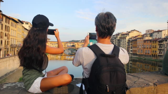 father and his teenage daughter taking photos of the ponte vecchio bridge in florence, italy - fotografieren stock-videos und b-roll-filmmaterial