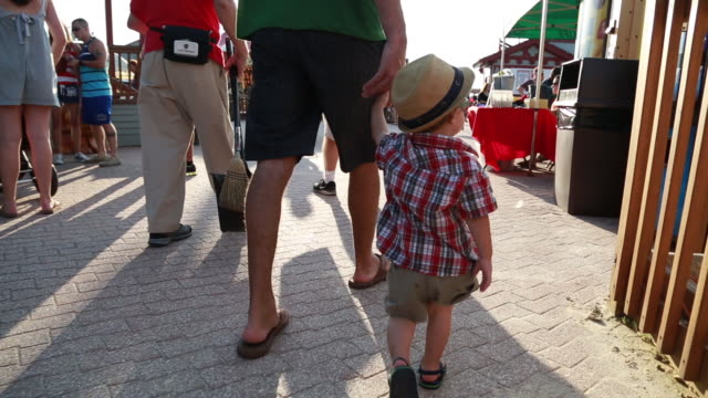 A father and his toddler son hold hands and walk through the Fantasy Island amusement park in Long Beach Island New Jersey