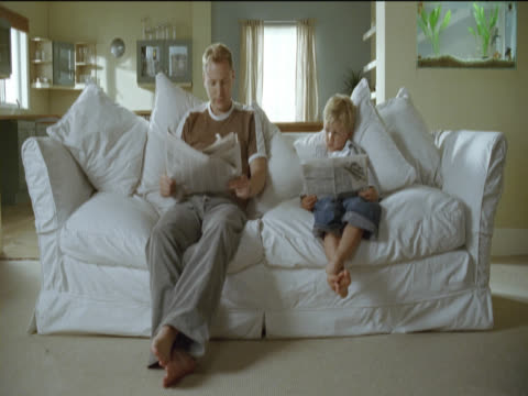 father and his young son sit side by side on the sofa reading newspapers and cross their legs in unison - side by side stock videos & royalty-free footage