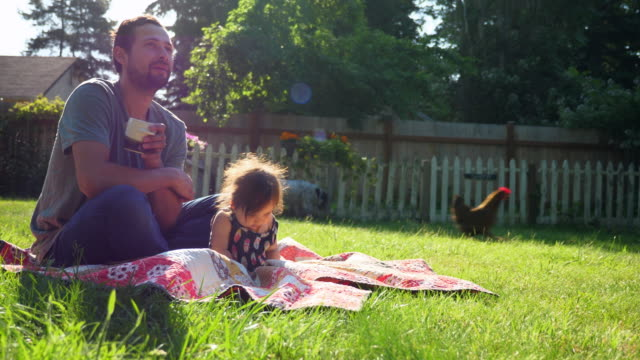 MS Father and infant daughter sitting together on blanket in backyard on summer morning