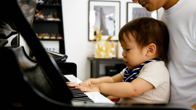 Father and little baby boy playing piano at home