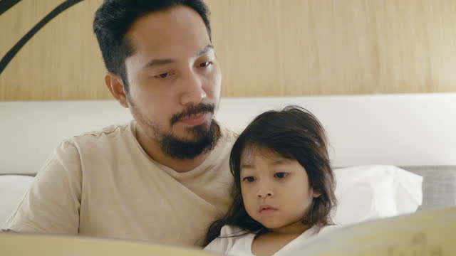 father and little girl read story book in bed. - storytelling stock videos & royalty-free footage