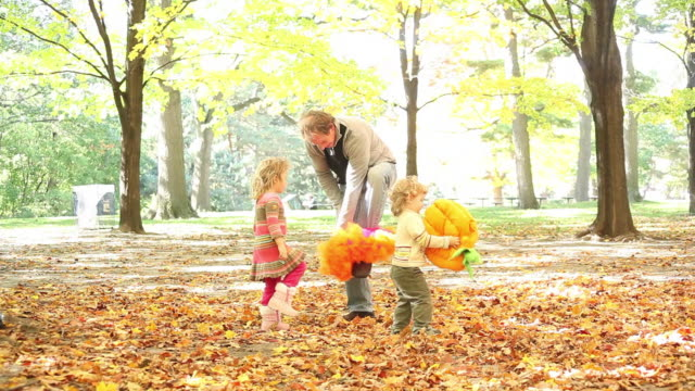 ms father and little girls both of them dancing amid fallen leaves as little boy runs around / toronto, ontario, canada - kelly mason videos stock videos & royalty-free footage