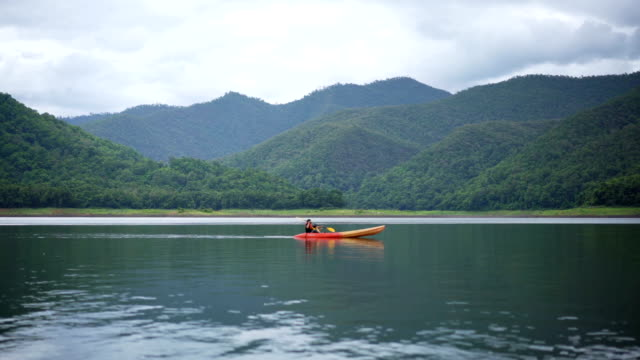 4K WS Father and little son kayaking on a lake during travel in Asia.