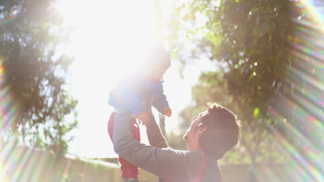 father and little son playing in the garden in sunny day - modern manhood stock videos & royalty-free footage