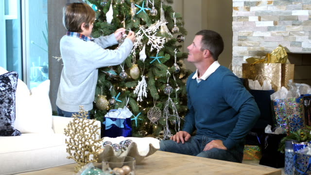 father and mixed race son decorating christmas tree - decorating the christmas tree stock videos & royalty-free footage