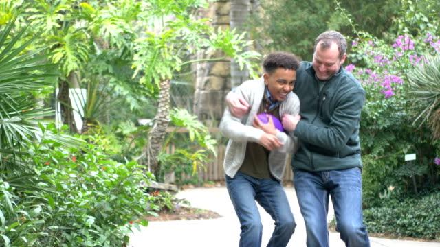 vidéos et rushes de père et fils mélangé de course jouant avec le football - jouer à la bagarre