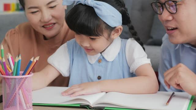 父と母は娘たちに書き、発展し,創造性を発揮し,楽しく学ぶことを教えるのを手伝っています。 - 美術工芸品点の映像素材/bロール