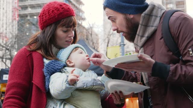 Father and mother feed baby at outdoor street market.