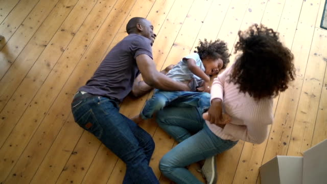 Father and mother tickling son on hardwood floor