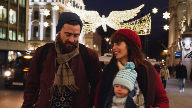 Father and mother with baby, are walking in shopping street with christmas lights.