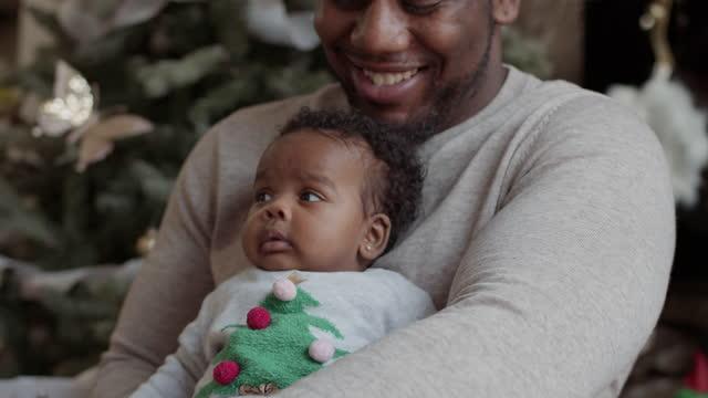 vídeos y material grabado en eventos de stock de un vínculo de padre y bebé recién nacido el día de navidad - genderblend