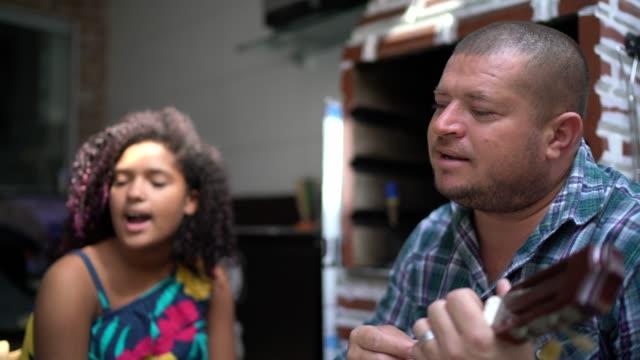vídeos de stock, filmes e b-roll de pai e irmãos tocando música em casa - 40 44 anos