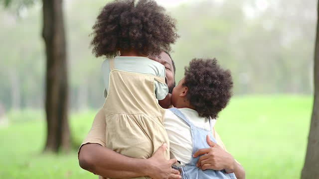 a father and son, a black daughter, were playing in the park having fun. everyone's faces were smiling at the time of happiness that all were spent together. - young family stock videos & royalty-free footage