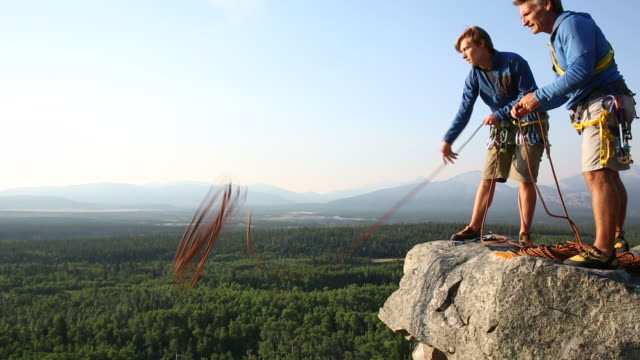 father and son arrange rope for climbing outing - jacket stock videos & royalty-free footage