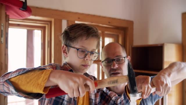自宅で家具を組み立てる父と息子 - ロールモデル点の映像素材/bロール