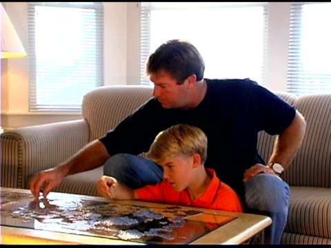father and son assembling puzzle - see other clips from this shoot 1335 stock videos and b-roll footage