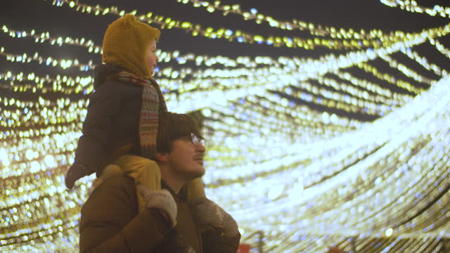 father and son at a christmas market - fairy lights stock videos & royalty-free footage