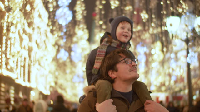father and son at a christmas market - christmas market stock videos & royalty-free footage