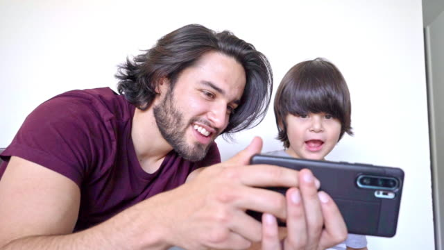father and son at home, making a video call during covid-19 - connection in process stock videos & royalty-free footage