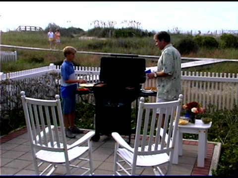 father and son at patio grill as mother and daughter walk towards them on a boardwalk. - see other clips from this shoot 1335 stock videos and b-roll footage