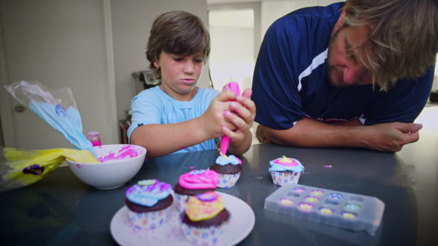Father and son bake cupcakes - candy on the top