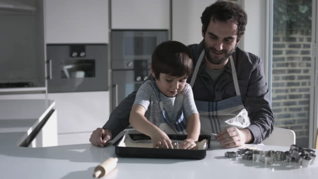 father and son baking biscuits - genderblend stock videos & royalty-free footage