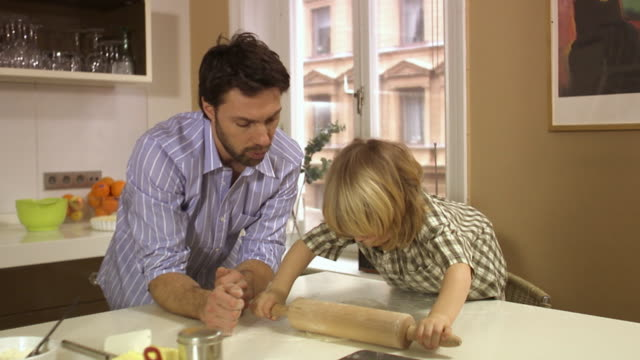 Father and son baking using a rolling-pin Stockholm Sweden.