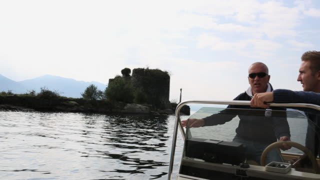 vidéos et rushes de father and son boat past island castle on lake maggiore - aller tranquillement