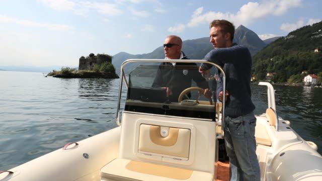 father and son boat past island castle on lake maggiore - sohn stock-videos und b-roll-filmmaterial