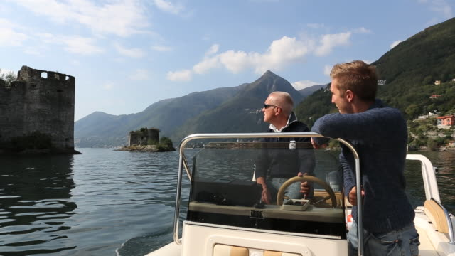 stockvideo's en b-roll-footage met father and son boat past island castle on lake maggiore - rondrijden