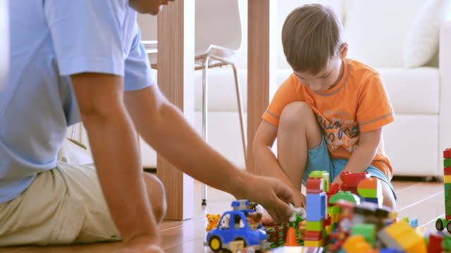 Father and son building with plastic bricks on the floor