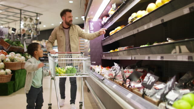 Father and son buying fruit and vegetable in grocery store