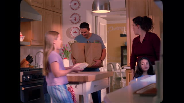 vidéos et rushes de a father and son carry in the groceries, while the girls help their mother put dishes away in a cupboard. - placard