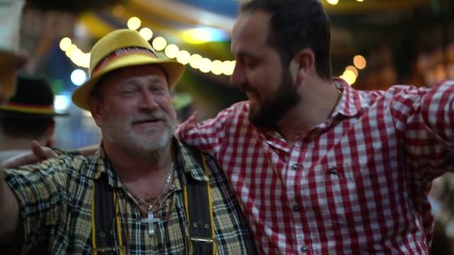 father and son celebrating at oktoberfest in blumenau, santa catarina, brazil - oktoberfest stock videos & royalty-free footage