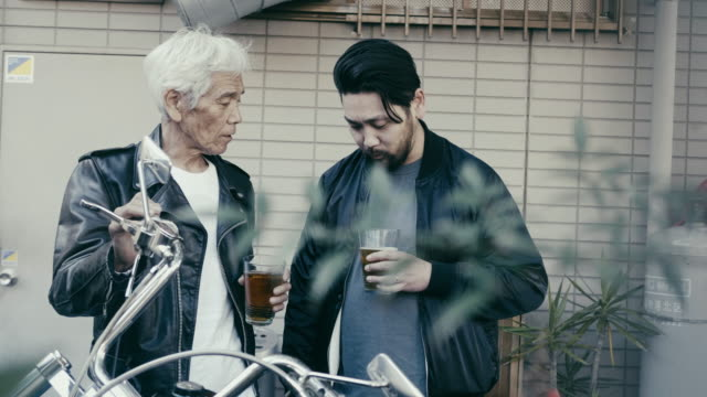 father and son celebrating purchase of a new motorcycle - leather jacket stock videos & royalty-free footage