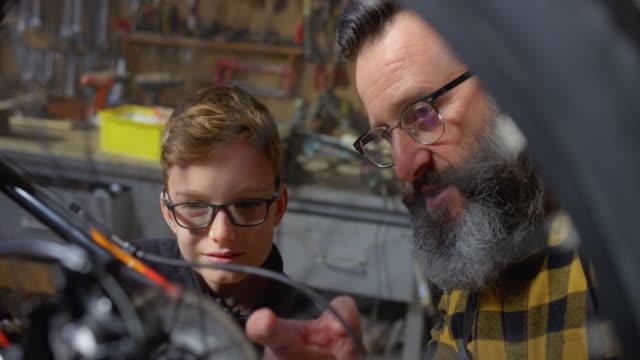 vídeos y material grabado en eventos de stock de slo mo padre e hijo revisando la bicicleta en su taller de casa - garaje