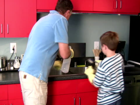 stockvideo's en b-roll-footage met father and son cleaning together - afwashandschoen
