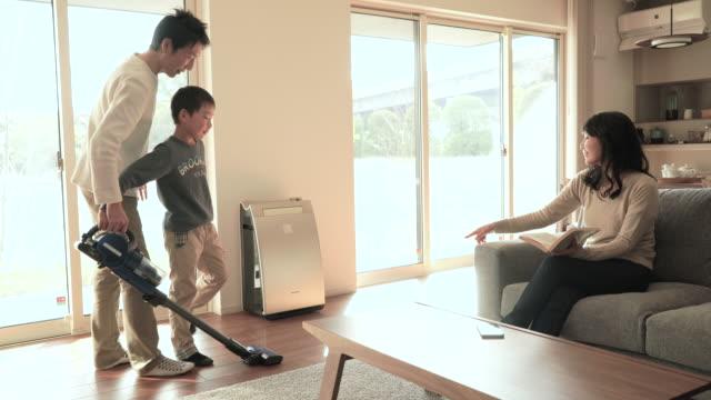 Far och son rengöring med dammsugare