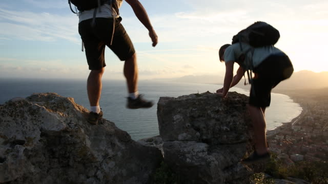 Father and son climb rock and look out over village and sea