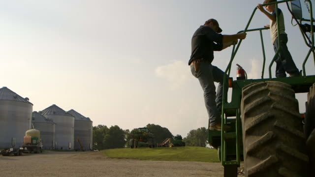 Father and son climbing off tractor