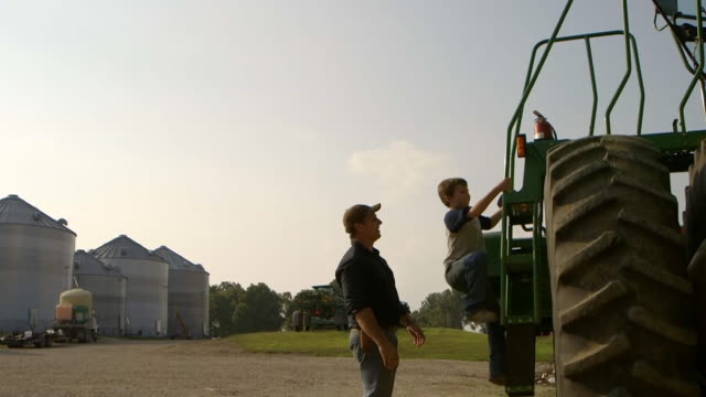Father and son climbing onto tractor