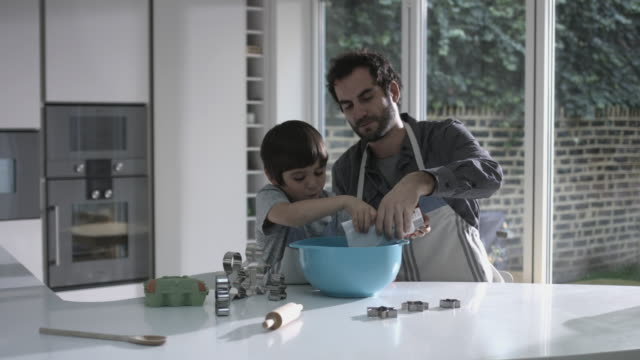father and son cooking biscuits - genderblend stock videos & royalty-free footage