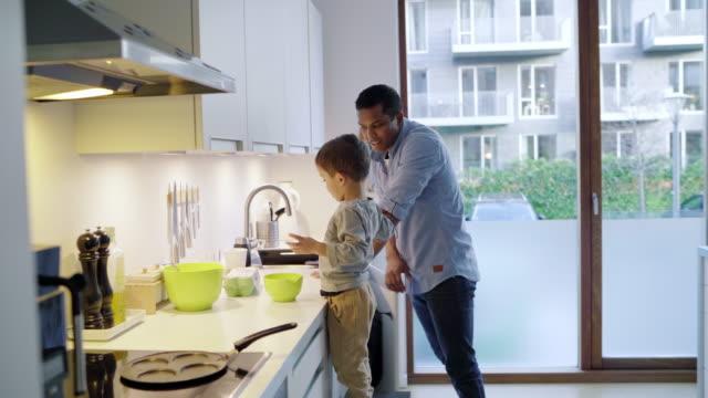 vidéos et rushes de father and son cracking eggs - son