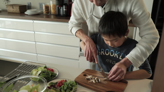 father and son cutting the mushroom - domestic kitchen stock videos & royalty-free footage