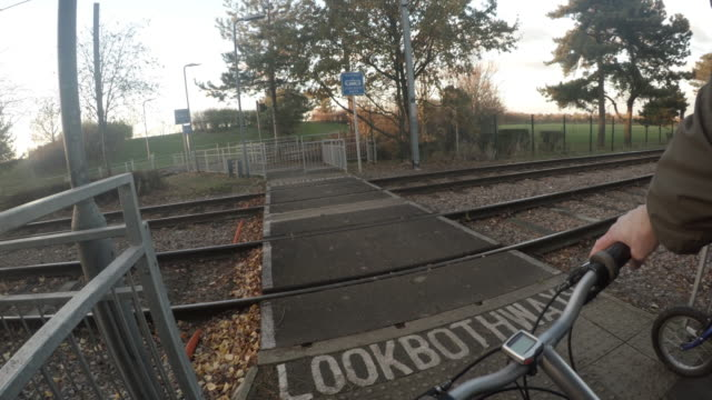father and son cycling across tram tracks - tram point of view stock videos and b-roll footage