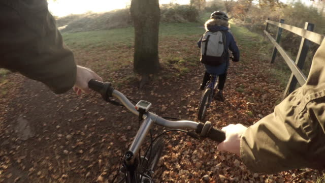 father and son cycling through a park - point of view stock videos & royalty-free footage