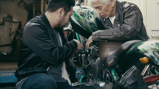 father and son discussing about motorcycles - son stock videos & royalty-free footage