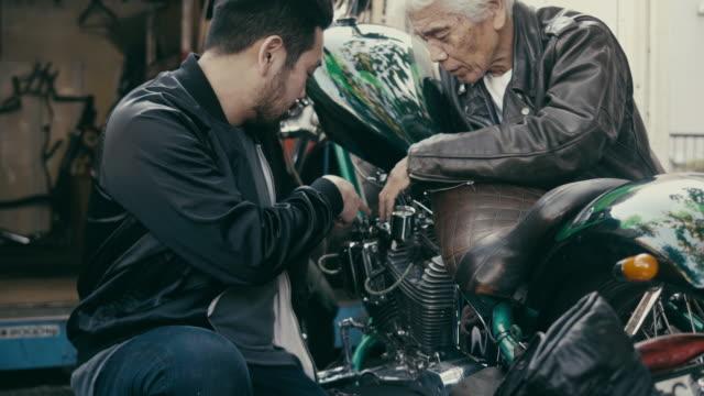 stockvideo's en b-roll-footage met vader en zoon die over motorfietsen bespreken - zoon