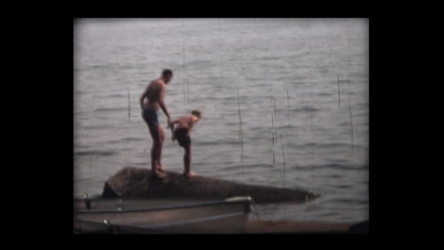 1966 father and son dive into lake - swimming trunks stock videos & royalty-free footage